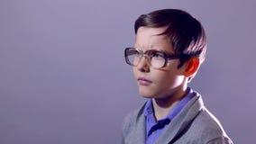 El retrato del empollón del adolescente del muchacho piensa los vidrios del colegial del problema almacen de metraje de vídeo