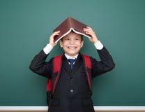 El retrato del escolar en traje negro en fondo verde de la pizarra con la mochila roja puso el libro en la cabeza, concepto de la Fotografía de archivo