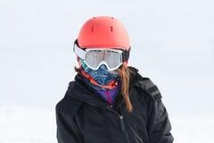 El retrato del esquiador de la muchacha envolvió para arriba caliente en engranaje del esquí con h anaranjado Imágenes de archivo libres de regalías