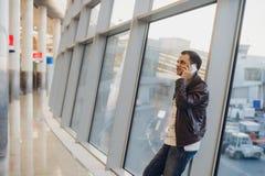 El retrato del estilo sport que lleva de la persona hermosa joven viste la ventana cercana derecha en terminal de aeropuerto mode Imágenes de archivo libres de regalías