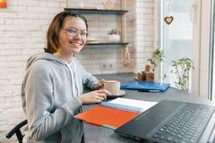 El retrato del estudiante joven, el estudiante de la escuela secundaria en cafetería con el ordenador portátil y la taza de café, imagen de archivo libre de regalías