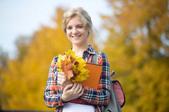 El retrato del estudiante joven femenino sonriente al aire libre que lleva a cabo amarillo se va Fotos de archivo