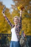 El retrato del estudiante joven femenino sonriente al aire libre que lleva a cabo amarillo se va Fotografía de archivo