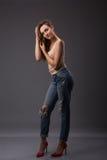 El retrato del estudio del modelo bonito de la mujer con las piernas largas del cuerpo asombroso que inclinan agains empareda los fotografía de archivo libre de regalías