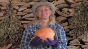 El retrato del granjero de la mujer en el fondo de la leña está sosteniendo una calabaza madura almacen de video