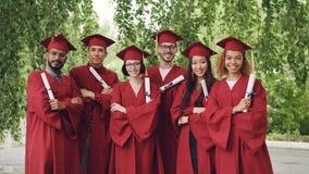 El retrato del grupo de estudiantes de graduación que llevaban a cabo los diplomas y la situación al aire libre con los brazos cr metrajes
