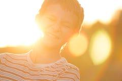 El retrato del Headshot de atornillar encima de los ojos que ríen al adolescente en la puesta del sol caliente hecha excursionism Fotos de archivo