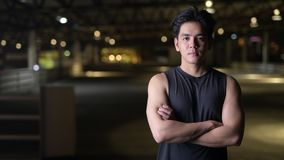 El retrato del hombre asiático hermoso feliz joven con los brazos cruzó al aire libre en la noche almacen de video
