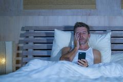 El retrato del hombre atractivo joven que mentía en cama cansó y relajado usando el teléfono móvil que miraba soñoliento su dormi fotografía de archivo