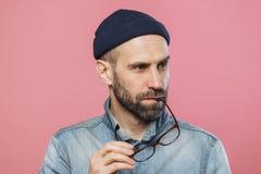 El retrato del hombre barbudo pensativo saca los vidrios, lleva la chaqueta elegante del dril de algodón y el sombrero, aislados  imágenes de archivo libres de regalías