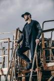 El retrato del hombre bien vestido de moda se coloca en una escalera oxidada del metal Fotos de archivo libres de regalías