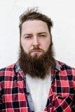 El retrato del hombre brutal fuerte con una barba vestida en una camisa comprobada en el fondo blanco fotos de archivo libres de regalías
