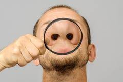 El retrato del hombre caucásico con la lupa hace la cara de la diversión imagen de archivo