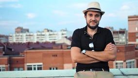 El retrato del hombre caucásico feliz en sombrero con los brazos cruzó al aire libre en el tejado o el balcón almacen de video