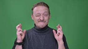 El retrato del hombre de mediana edad con la barba que gesticula los cruzar-fingeres firma para mostrar esperanza en fondo verde metrajes