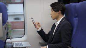 El retrato del hombre de negocios coreano que está mecanografiando el mensaje en su teléfono móvil mientras que viaja en tren almacen de video
