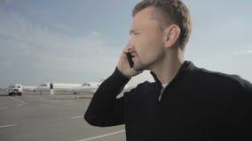 El retrato del hombre de negocios habla en el teléfono en aeropuerto metrajes