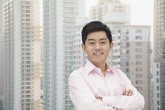 El retrato del hombre de negocios joven en camisa del botón abajo con los brazos cruzó, rascacielos en fondo Fotos de archivo