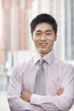 El retrato del hombre de negocios joven sonriente con los brazos cruzó al aire libre, Pekín, China Imágenes de archivo libres de regalías