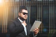 El retrato del hombre de negocios lee noticias en la tableta fotografía de archivo libre de regalías