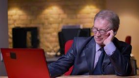 El retrato del hombre de negocios mayor en el traje formal que trabaja con el ordenador portátil inclina a mano estar cansado en  metrajes
