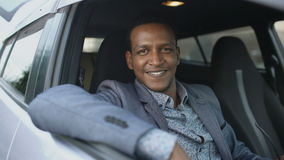 El retrato del hombre de negocios serio que se sentaba dentro del coche puso de gafas de sol y de la sonrisa en cámara al aire li