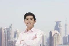 El retrato del hombre de negocios sonriente confiado joven en camisa del botón abajo con los brazos cruzó, horizonte de Shangai en Foto de archivo