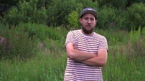 El retrato del hombre divertido barbudo joven con el casquillo da vuelta alrededor y cruza las manos almacen de metraje de vídeo