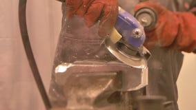 El retrato del hombre en boilersuit en empresa corta una pieza de metal con la amoladora de ángulo metrajes