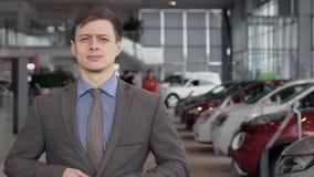 El retrato del hombre en chaqueta gris y la camisa azul en el coche del concesionario de automóviles se centran Cámara lenta almacen de video