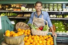 El retrato del hombre en supermercado con la cesta vegetal que coloca naranjas cercanas atasca Imágenes de archivo libres de regalías
