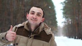 El retrato del hombre en una chaqueta está mostrando el pulgar para arriba en bosque del invierno almacen de video