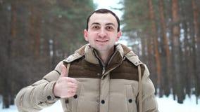 El retrato del hombre en una chaqueta está mostrando el pulgar para arriba El hombre se coloca en bosque del invierno almacen de metraje de vídeo