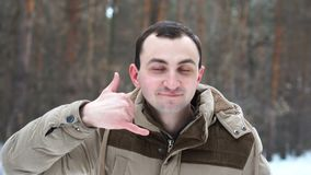 El retrato del hombre está mostrando me llama gesto en bosque del invierno almacen de metraje de vídeo