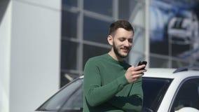 El retrato del hombre hermoso utiliza su smartphone y soportes cerca de su coche almacen de metraje de vídeo