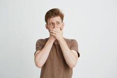 El retrato del hombre joven asustado asustado sorprendido que mira en boca cerrada lateral con entrega el fondo blanco Imagen de archivo