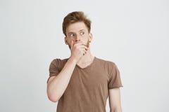 El retrato del hombre joven asustado asustado sorprendido que mira en boca cerrada lateral con entrega el fondo blanco Fotografía de archivo