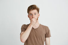 El retrato del hombre joven asustado asustado sorprendido que mira la boca cerrada de la cámara con entrega el fondo blanco Foto de archivo libre de regalías