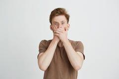 El retrato del hombre joven asustado asustado sorprendido que mira la boca cerrada de la cámara con entrega el fondo blanco Fotografía de archivo libre de regalías
