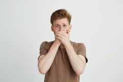 El retrato del hombre joven asustado asustado sorprendido que mira la boca cerrada de la cámara con entrega el fondo blanco Foto de archivo