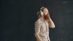 El retrato del hombre joven barbudo pone los auriculares y el baile mientras que escuche la música en fondo negro almacen de metraje de vídeo