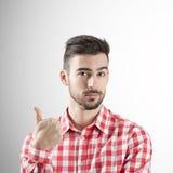 El retrato del hombre joven con los pulgares sube gesto Imágenes de archivo libres de regalías