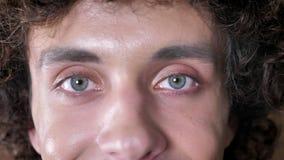 El retrato del hombre joven con el pelo rizado y los ojos azules que miran la cámara, tiro cercano del ` s del hombre observa almacen de video