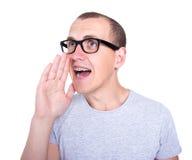 El retrato del hombre joven divertido en vidrios con los apoyos en los dientes llama Imagenes de archivo