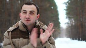 El retrato del hombre joven en chaqueta está aplaudiendo al aire libre El hombre se coloca en bosque del invierno almacen de video