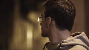 El retrato del hombre joven en vidrios fuera de la respiración da vuelta alrededor en backstreet metrajes