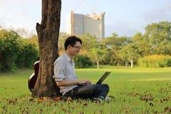El retrato del hombre joven feliz está sonriendo con un ordenador portátil en parque de la ciudad Imagenes de archivo