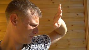 El retrato del hombre joven que parece ausente y que cubre su cara con una mano contra el ` s del sol irradia almacen de metraje de vídeo