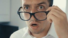 El retrato del hombre joven se sorprende y saca sus vidrios en choque Él está preocupado de ver almacen de metraje de vídeo