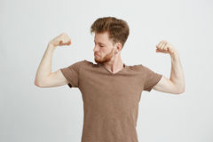 El retrato del hombre juguetón sano joven que mira su bíceps muscles la jactancia sobre el fondo blanco Fotos de archivo